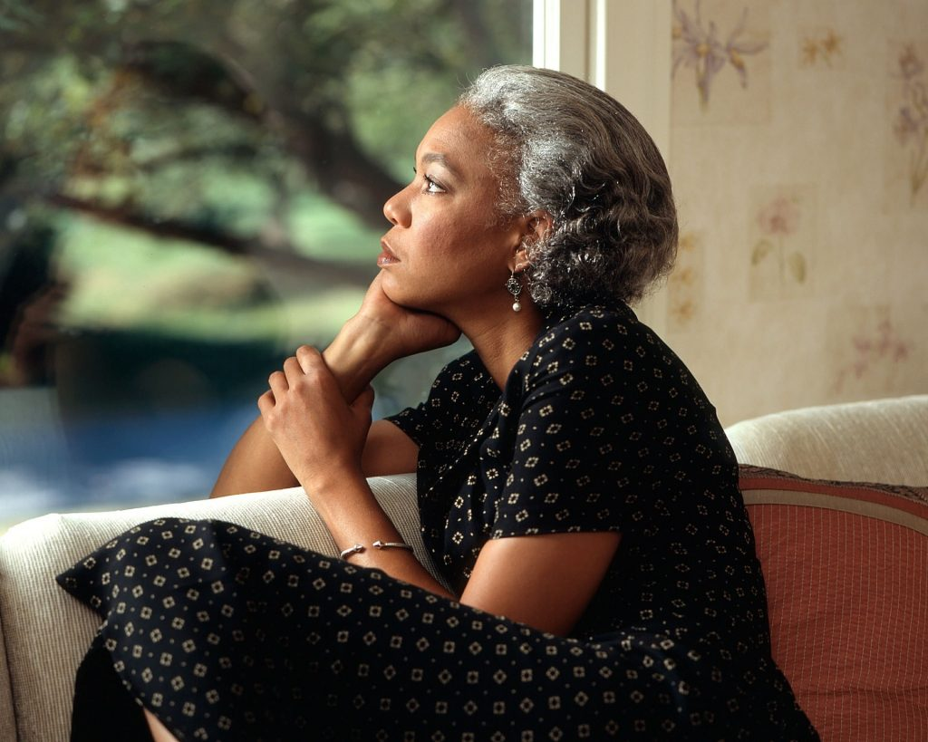 old woman staring out window pensively